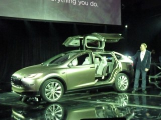 Tesla CEO Elon Musk, demonstrating the Model X third-row seat and falcon doors